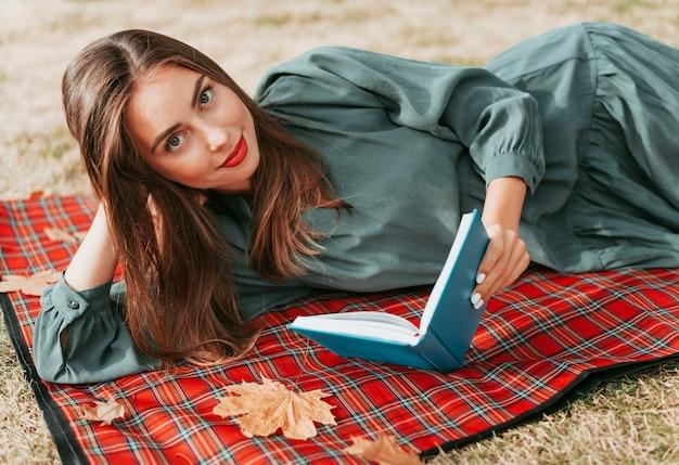 Vrouw genieten van een boek op een picknickkleed Gratis Foto