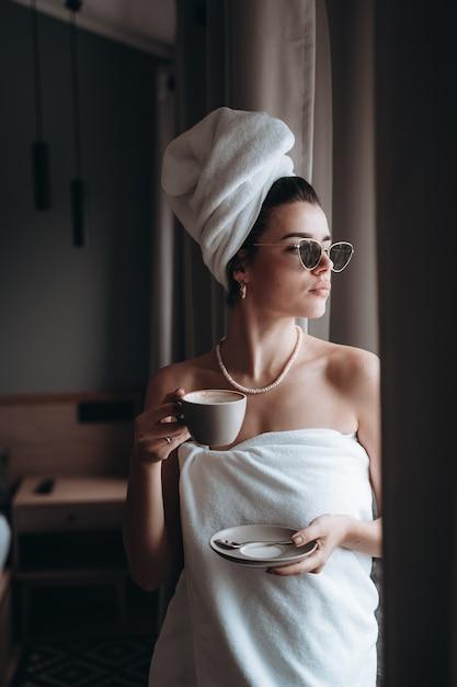 Vrouw gewikkeld in een handdoek koffie drinken Gratis Foto