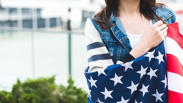 Vrouw gewikkeld in grote amerikaanse vlag Gratis Foto