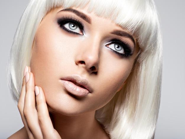 Vrouw gezicht met mode zwarte make-up van oog en lange zwarte wimpers. Gratis Foto