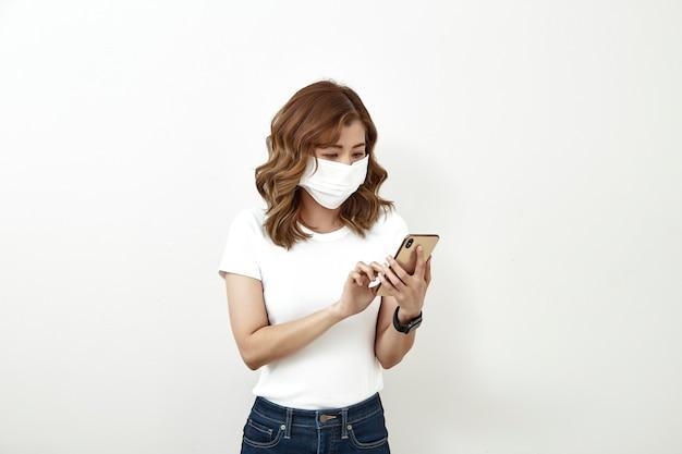Vrouw gezichtsmasker met behulp van de smartphone Premium Foto