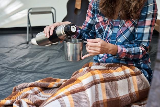Vrouw gieten thee uit thermos in camping tent Premium Foto