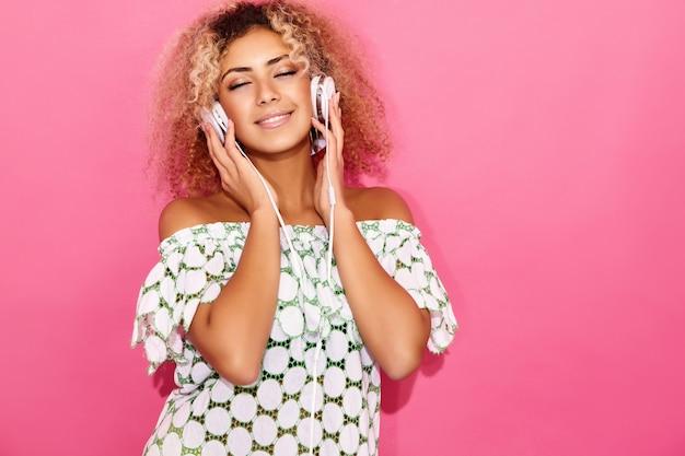 Vrouw glimlacht en luistert naar muziek in een koptelefoon Gratis Foto