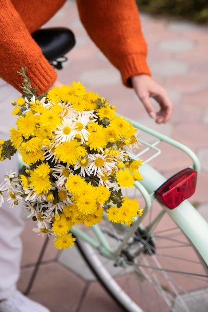 Vrouw grijpen fiets met boeket bloemen buitenshuis Gratis Foto