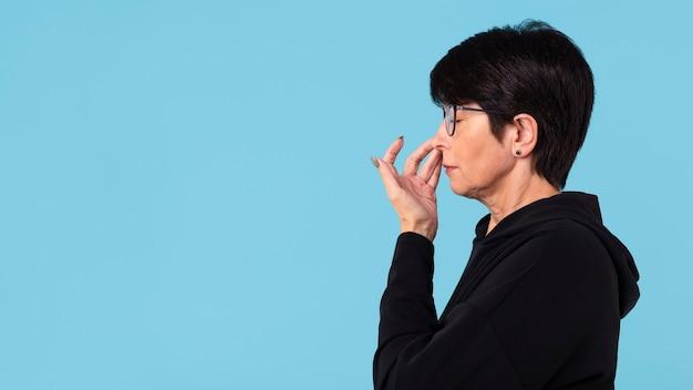 Vrouw haar neus met kopie ruimte aan te raken Gratis Foto