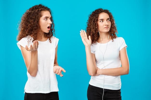 Vrouw haatdragend naar haar zus tweeling in hoofdtelefoons over blauw. Gratis Foto