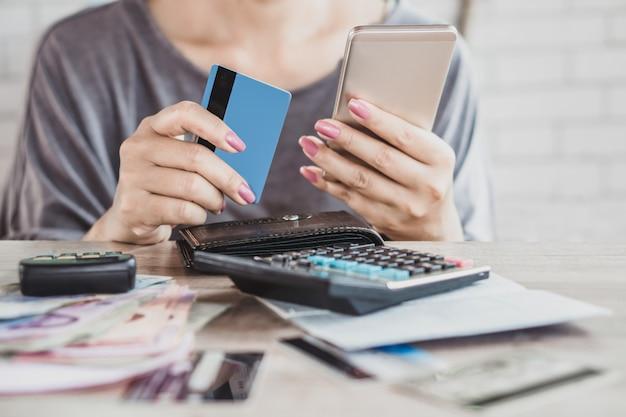 Vrouw hand berekenen creditcard schuld met slimme telefoon Premium Foto