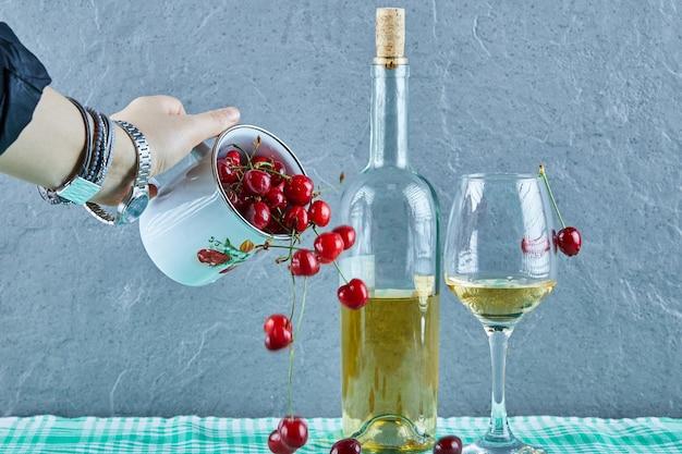 Vrouw hand gooien kopje kersen en een fles witte wijn met glas op blauwe ondergrond Gratis Foto