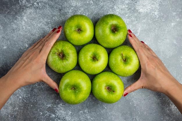 Vrouw hand met bos appels op marmer. Gratis Foto