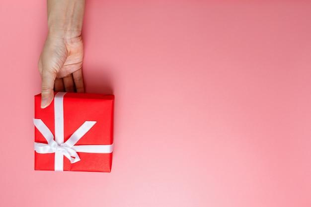 Vrouw hand met cadeau verpakt en versierd met strik Premium Foto