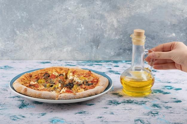 Vrouw hand met een glazen fles olie in de buurt van hete pizza op een marmeren achtergrond. Gratis Foto
