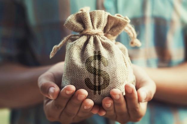 Vrouw hand met geld tas. concept besparing financiën en boekhouding Premium Foto