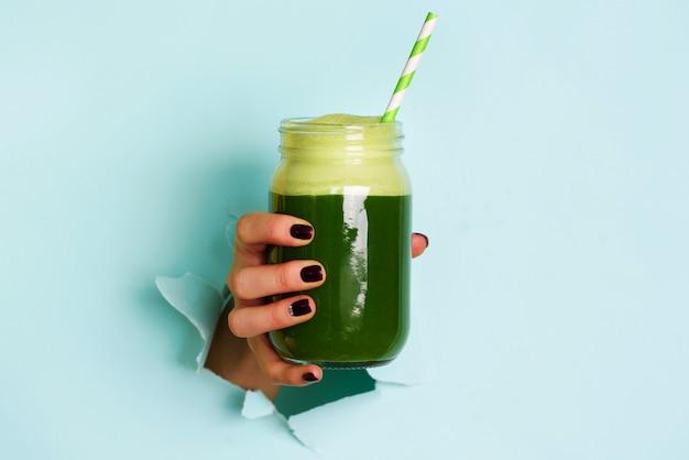 Vrouw hand met glazen pot van groene smoothie, vers sap tegen blauwe achtergrond. Premium Foto