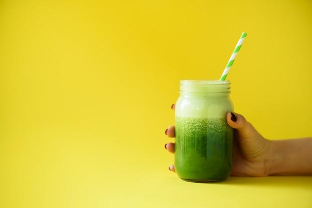 Vrouw hand met glazen pot van groene smoothie, vers sap tegen gele achtergrond. Premium Foto