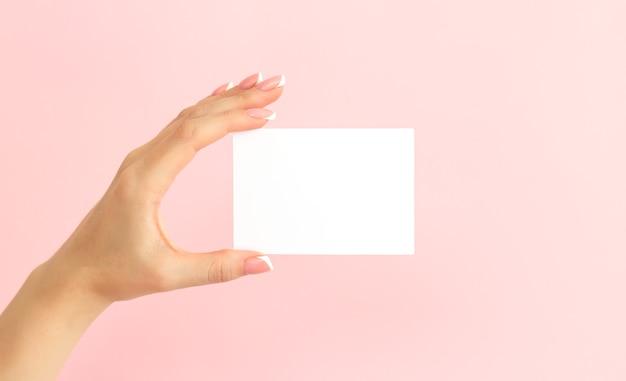 Vrouw hand met lege witte visitekaartje, korting of flyer op roze achtergrond Premium Foto