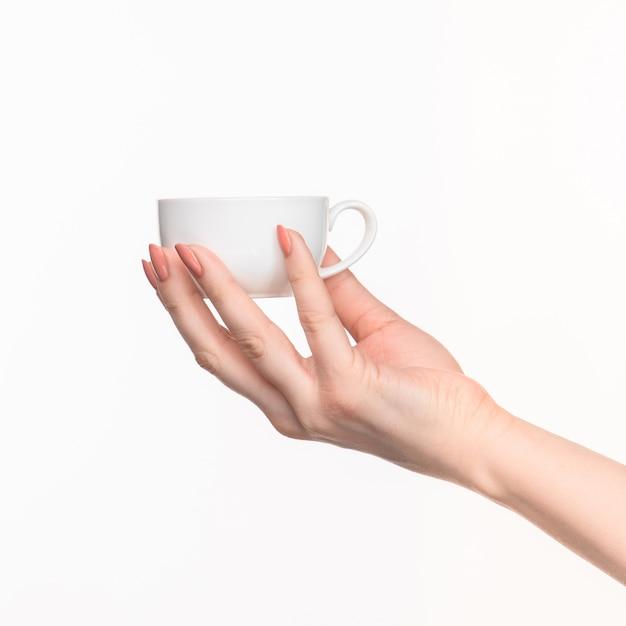 Vrouw hand met perfecte witte kop op witte achtergrond Gratis Foto