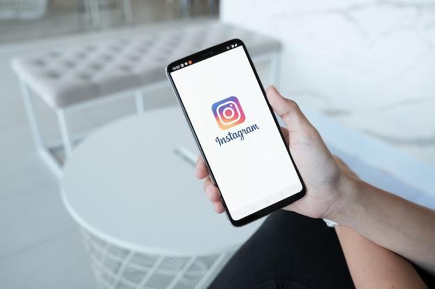 Vrouw hand met smartphone met login-scherm van instagram-applicatie. instagram is het grootste en populairste sociale netwerk voor foto's Premium Foto