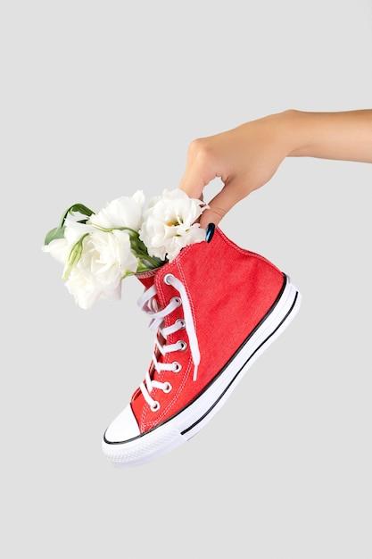 Vrouw hand met trendy rode sneaker met bloemen Premium Foto