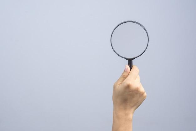 Vrouw hand met vergrootglas Premium Foto
