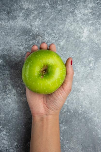 Vrouw hand met verse appel op marmer. Gratis Foto