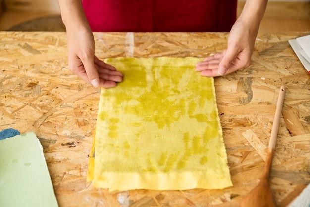 Vrouw hand op schimmel bedekt met gele stof Gratis Foto