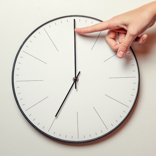 Vrouw hand stop tijd op een ronde klok, vrouwelijke vinger neemt de minuut pijl van de klok terug, tijdbeheer en deadline Premium Foto
