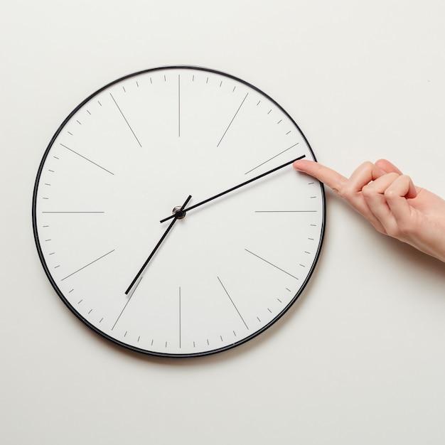 Vrouw hand stop tijd op ronde klok, vrouwelijke vinger neemt de minuut pijl van de klok terug, time management en deadline concept Premium Foto