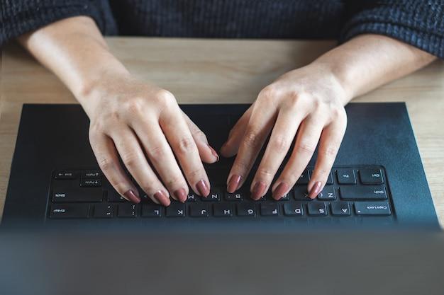 Vrouw hand typen op toetsenbord computer laptop Premium Foto