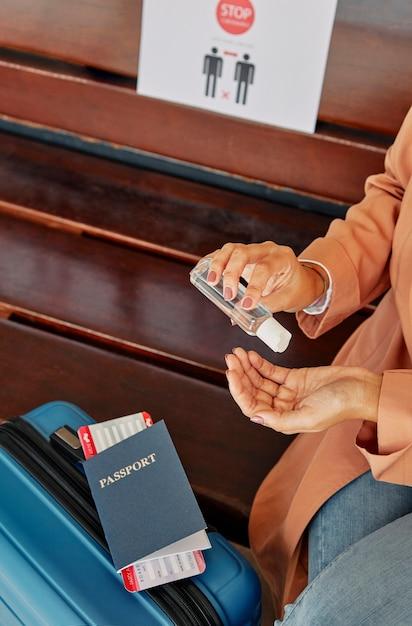 Vrouw handdesinfecterend middel toe te passen op de luchthaven tijdens pandemie Gratis Foto