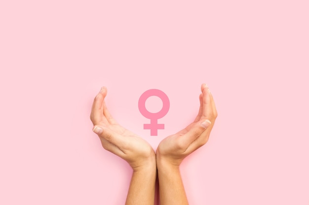 Vrouw handen beschermen vrouwelijke teken op een roze achtergrond Premium Foto