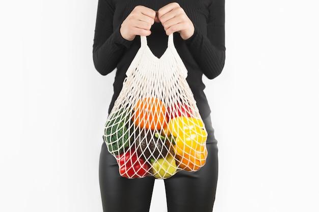 Vrouw handen met een boodschappentas met groenten fruit op wit Premium Foto