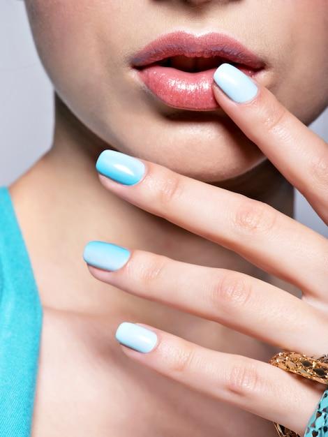 Vrouw handen nagels manicure mode blauwe sieraden. Gratis Foto