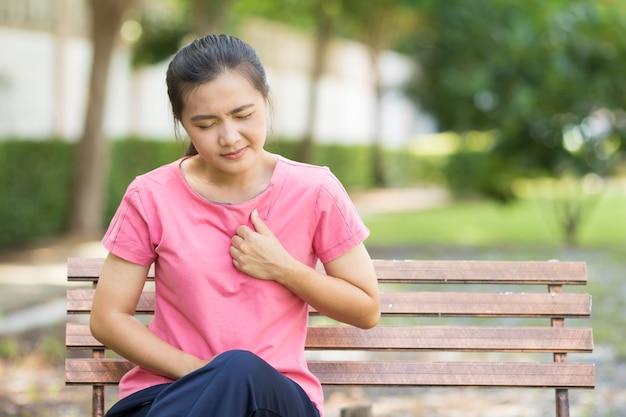 Vrouw heeft pijn op de borst in de tuin Premium Foto