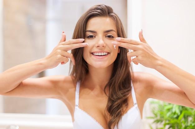 Vrouw heeft plezier tijdens het aanbrengen van een vochtinbrengende crème op het gezicht Gratis Foto
