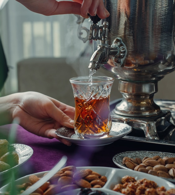 Vrouw heet water in glas gieten met zwarte thee uit samowar Gratis Foto