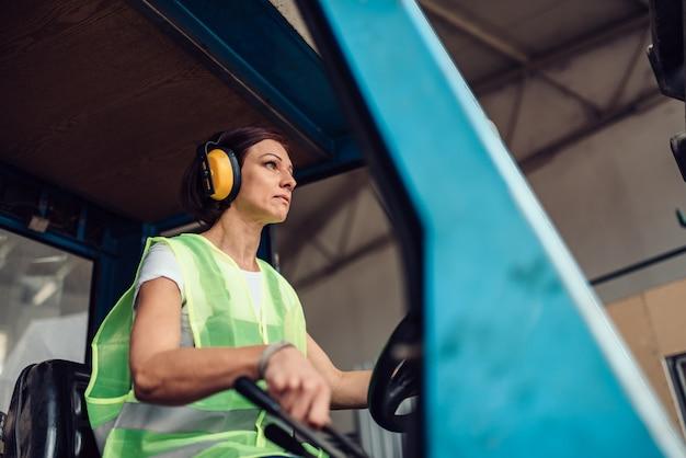 Vrouw heftruck operator rijden voertuig Premium Foto