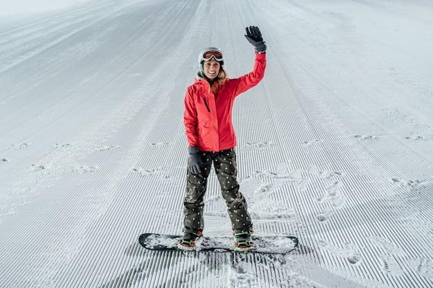 Vrouw helm met snowboard dragen op de skipiste. avond rijden Premium Foto