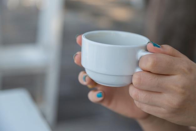Vrouw het drinken koffie ter beschikking met onduidelijk beeld baclground Premium Foto