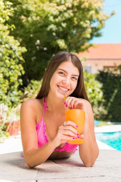Vrouw het drinken sap terwijl het liggen op poolrand Gratis Foto