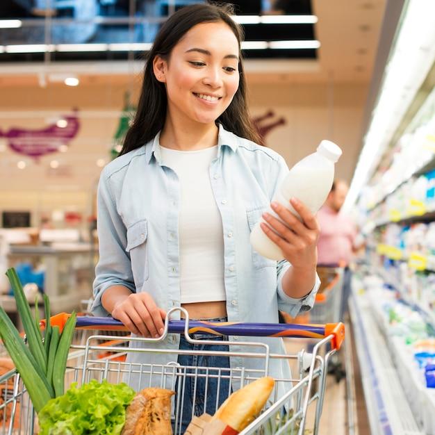 Vrouw het inspecteren fles melk bij kruidenierswinkelopslag Premium Foto
