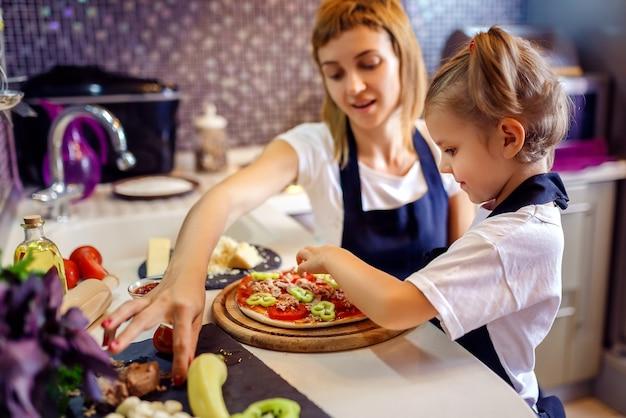 Vrouw het koken met meisje Premium Foto