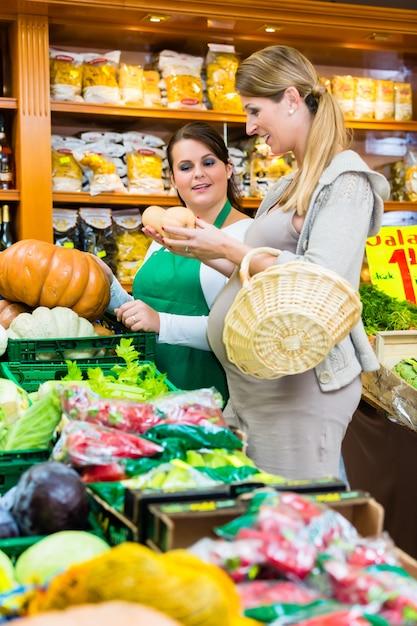 Vrouw het kopen pompoen en groenten in delicatessen Premium Foto