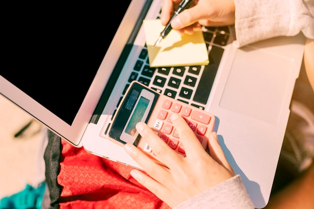 Vrouw het nemen van notities met de hand op laptop in zonnige dag Gratis Foto