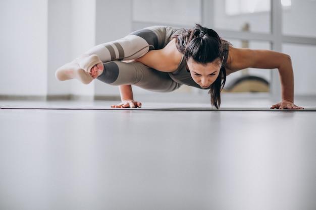Vrouw het praktizeren yoga in de gymnastiek op een mat Gratis Foto