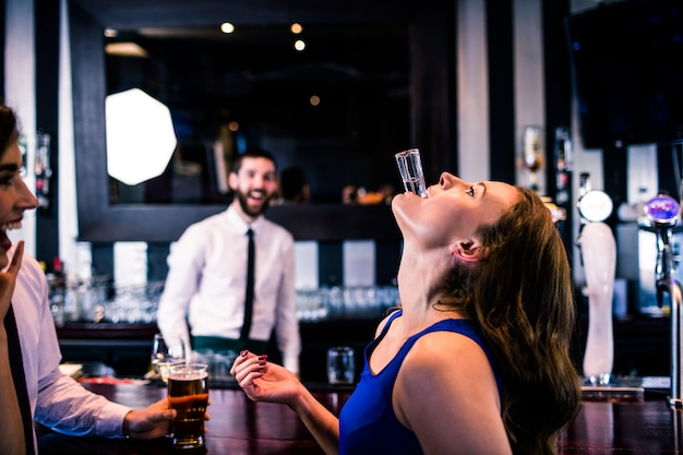 Vrouw het spelen met haar schot in een bar met vrienden Premium Foto