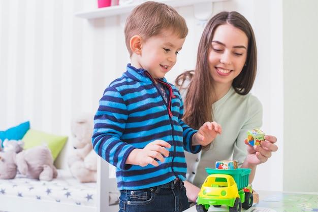 Vrouw het spelen stuk speelgoed auto met zoon Gratis Foto
