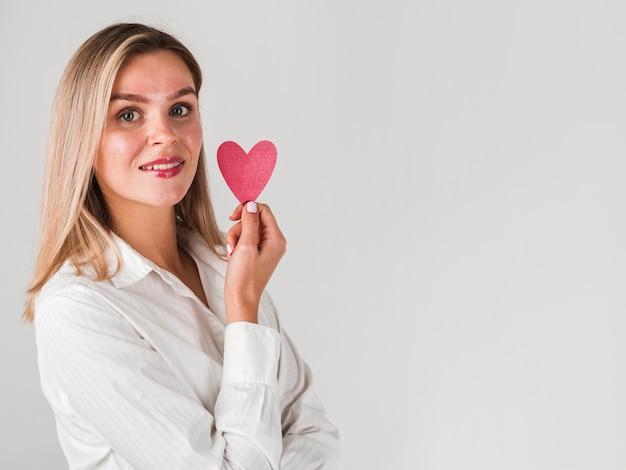 Vrouw het stellen met hart en exemplaarruimte Gratis Foto