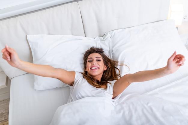 Vrouw het uitrekken zich in bed met haar opgeheven wapens. portret van aantrekkelijke mooie vrouw die van tijd in slecht na slaap genieten die onder deken liggen die het uitrekken houden die ogen houden gesloten maken. goede dag leven gezondheid Premium Foto