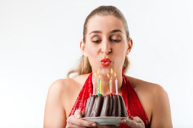 Vrouw het vieren verjaardag met cake en kaarsen Premium Foto