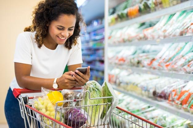 Vrouw het winkelen groenten bij de supermarkt Premium Foto